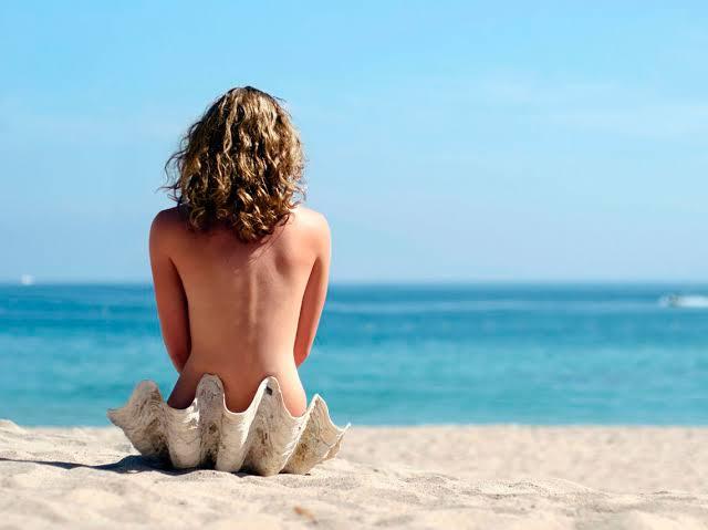 Chica desnuda en playa