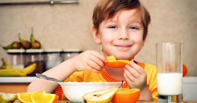 Niño desayunado fruta