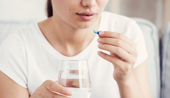 Mujer tomando ibuprofeno de Aurax medicamentos