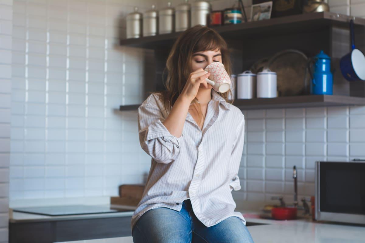 mujer bebiendo café en cocina