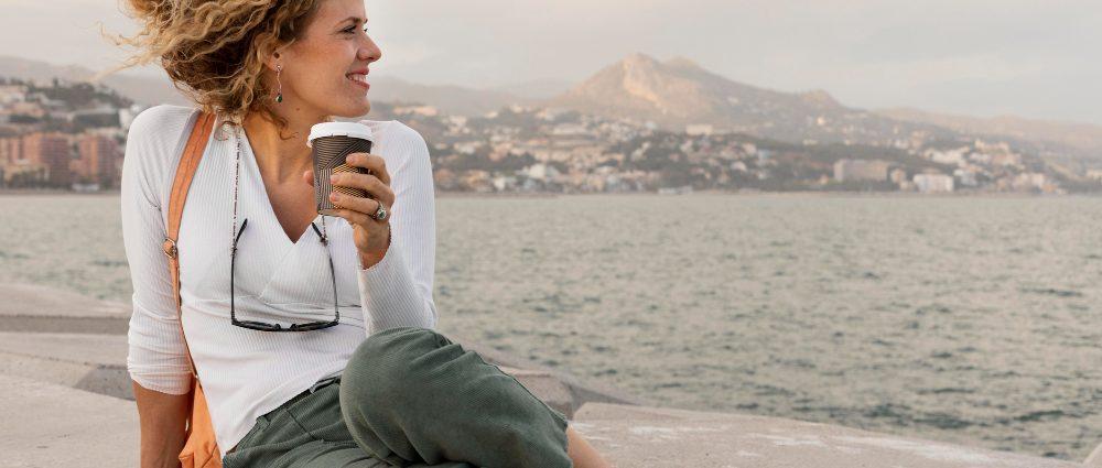 mujer-con-vaso-de-café-y-paisaje-de-fondo