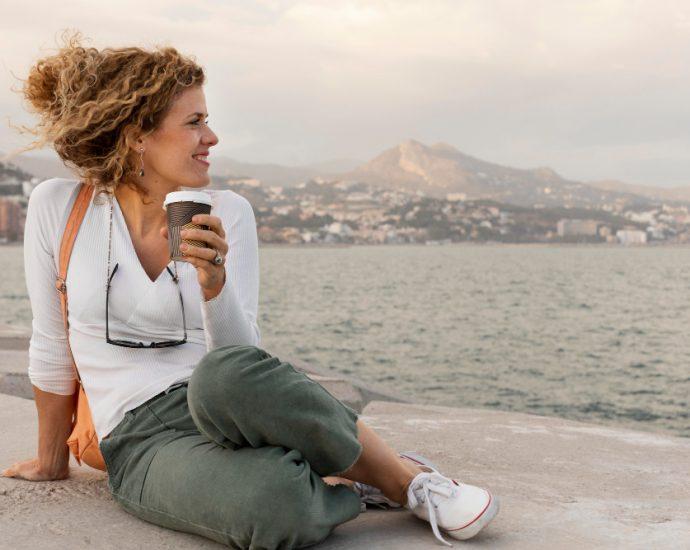 mujer con vaso de café y paisaje de fondo