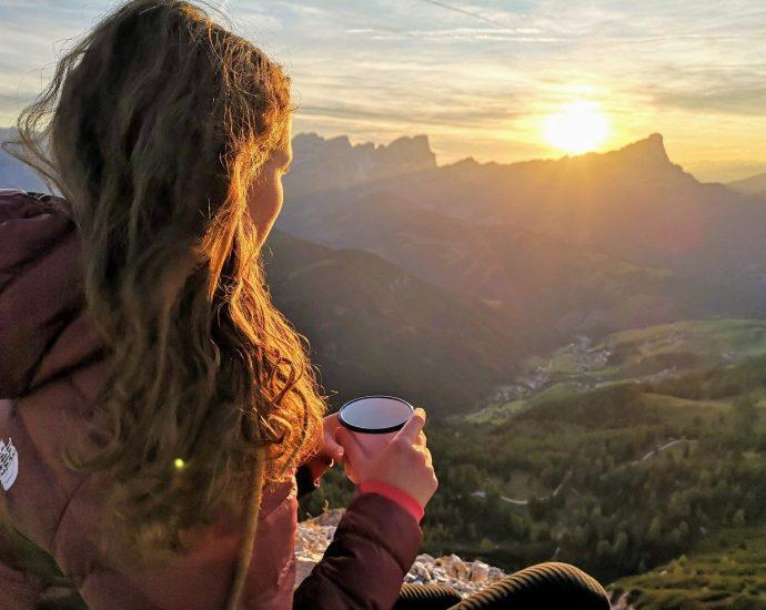 mujer en montaña bebiendo café viendo el medio ambiente