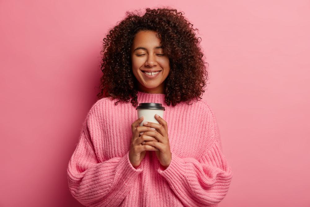 mujer-sonriendo-con-vaso-de-café-fondo-rosa