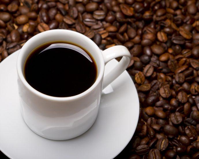 taza de café negro alrededor granos de café